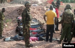 FILE - Kenyan military personnel stand near bodies lined up on the ground at a quarry site where attackers killed at least 36 workers in a village in Korome, outside the border town of Mandera, Dec. 2, 2014.