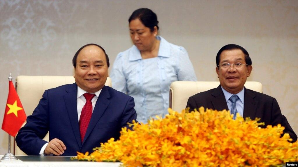 Thủ tướng Campuchia Hun Sen (phải) và Thủ tướng Việt Nam Nguyễn Xuân Phúc tại một lễ ký kết ở Phnompenh ngày 25/4/2017. Các đảng ở Campuchia từng tranh cãi về việc liệu Campuchia được 'hồi sinh' vào năm 1979 hay bị trao cho Việt Nam trong 10 năm chiếm đóng.