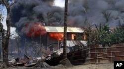 Khói bốc lên từ 1 căn nhà đang cháy ở Sittwe, Rakhine, Miến Điện, nơi bạo động giáo phái đang diễn ra, 12/6/2012