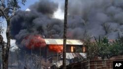 Lửa và khói bốc lên từ các tòa nhà bị đốt cháy trong các vụ bạo động sắc tốc ở Sittwe, thủ phủ của bang Rakhine ở tây bắc Miến Ðiện, ngày 12/6/2012