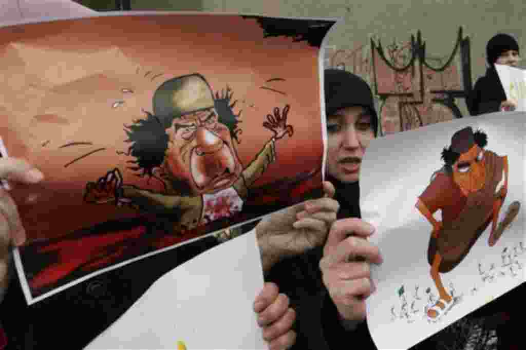 Demonstrators hold depictions of Libyan leader Moammar Gadhafi during a protest against the Libyan regime's crackdown on protestors, in front of the Libyan Embassy, Sarajevo, Bosnia, Wednesday, Feb. 23, 2011. (AP Photo/Sulejman Omerbasic)