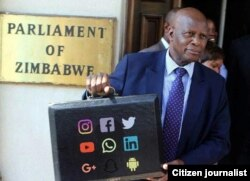 Chinamasa is shown in this meme displaying a big briefcase outside parliament. Check what's inscribed on the briefcase.