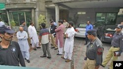 Pakistani security officials gather at the compound of the house of a abducted American citizen in Lahore, Pakistan, Aug. 13, 2011.