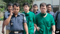 A Japanese doctor, front right, and the chief security officer of the Japanese embassy in Bangladesh, center, walk back from the morgue after the autopsy on the body of killed Japanese citizen Kunio Hoshi at Mahiganj village in Rangpur district, 300 kilom