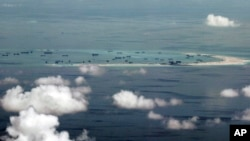 This photo taken through a window of a military plane shows China's apparent reclamation of Mischief Reef in the Spratly Islands in the South China Sea, May 11, 2015. (Ritchie B. Tongo/Pool Photo via AP)