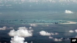 FILE - This photo taken through a window of a military plane shows Mischief Reef in the Spratly Islands in the South China Sea, May 11, 2015.