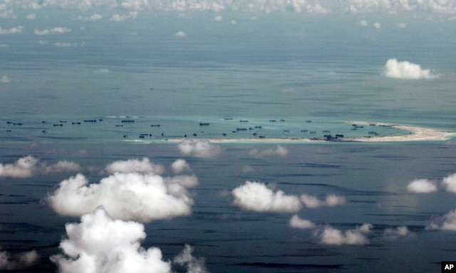 FILE - This photo taken through a window of a military plane shows China's apparent reclamation of Mischief Reef in the Spratly Islands in the South China Sea, May 11, 2015.