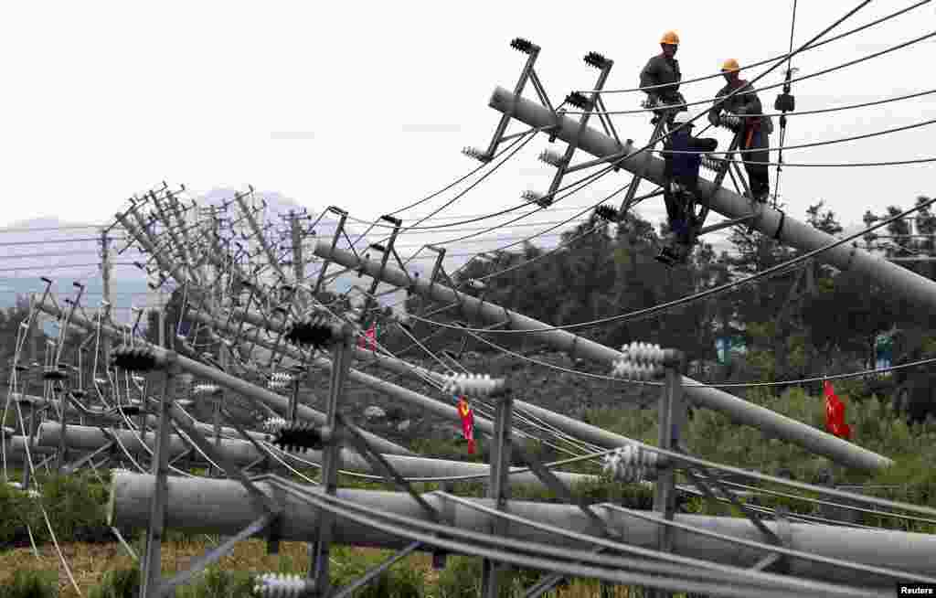 Laborers work to reconnect an electric circuit after pylons were turned over by Typhoon Haikui in Wenling, Zhejiang province, China, August 8, 2012.