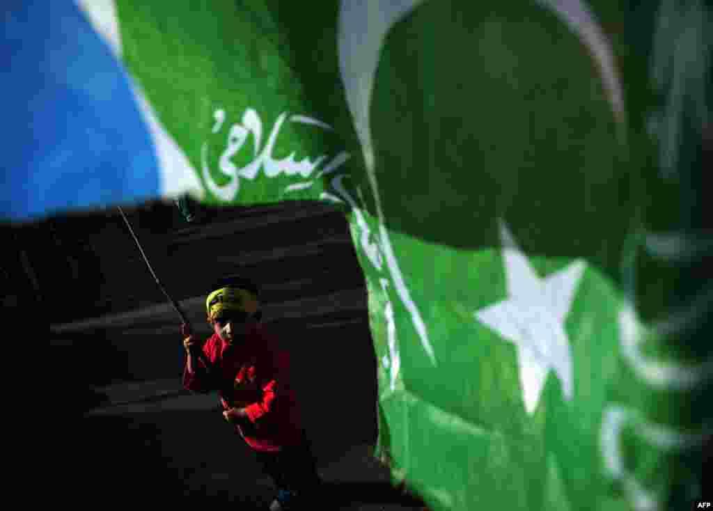 파키스탄 카라치에서 인도의 카슈미르 점령에 항의하는 시위가 벌어졌다. 한 어린이가 이슬람 극단주의 단체의 깃발을 흔들고 있다.