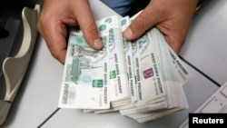 FILE - An employee counts Russian ruble bank notes at a private company's office in Krasnoyarsk, Siberia, Dec. 17, 2014.
