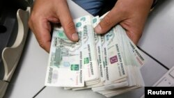 FILE - An employee counts Russian ruble bank notes at a private company's office in Krasnoyarsk, Siberia, Dec. 17, 2014. Sanctions linked to the Ukraine crisis could end up costing Russia 9 percent of its gross domestic product, says International Monetary Fund.