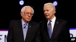 រូបឯកសារ៖ លោក Bernie Sanders សមាជិកព្រឹទ្ធសភាប្រចាំរដ្ឋ Vermont និងលោក Joe Biden អតីតអនុប្រធានាធិបតីអាមេរិក សន្ទនាគ្នាមុនការជជែកដេញដោលមួយ កាលពីថ្ងៃទី ២៥ ខែកុម្ភៈ ឆ្នាំ២០២០។