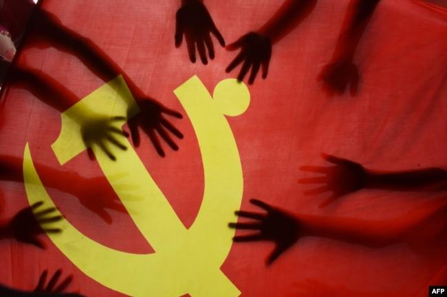 中國江蘇連雲港的一所小學校的學生在上中共黨史課時把手放在中共黨旗上。 (2020年6月28日)