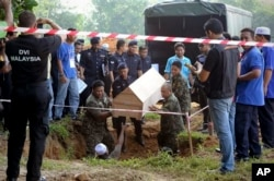 FILE - Malaysian officials provide Muslim burial to 21 human trafficking victims, believed to be Rohingya Muslim refugees, found in shallow graves in jungles bordering Thailand, in Kedah, Malaysia, June 22, 2015.