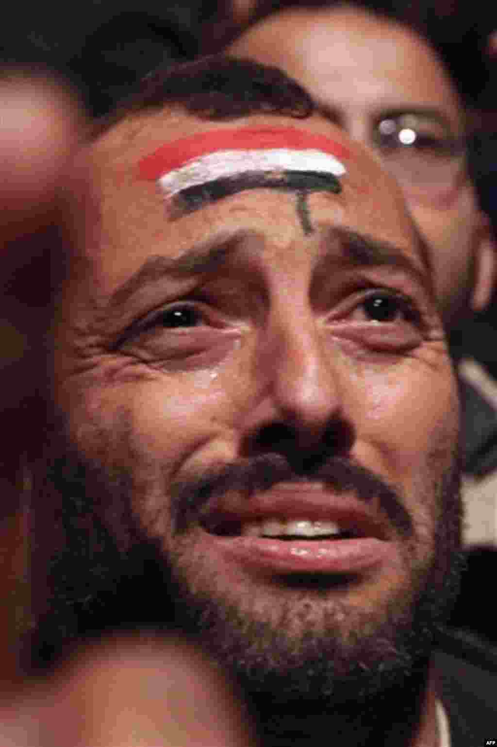 A protester is overcome by emotion as he and others prematurely celebrate prior to the televised speech of Egyptian President Hosni Mubarak, in which they believed he would step down, at the continuing anti-government demonstration in Cairo, Egypt Thursda