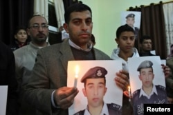 Jawdat Safi, brother of Islamic State captive Jordanian pilot Muath al-Kaseasbeh, holds a lit candle along with a poster of his brother as he takes part in a rally in support of al-Kaseasbeh at the family's headquarters in the city of Karak, Jan. 31, 2015
