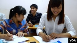 Pham Thi Trang, right, studies Japanese at a free language school set up by a street vendor in Hanoi, Vietnam, Aug. 7, 2014.