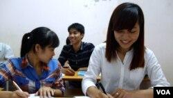ນາງ Pham Thi Trang, ຂວາ, ຮຽນພາສາຍີ່ປຸ່ນຟຣີ ຢູ່ໂຮງຮຽນ ທີ່ຈັດຕັ້ງຂຶ້ນ ໂດຍຄົນຂາຍຂອງແຄມທາງ ທີ່ຮາໂນ່ຍ, ວັນທີ 7 ສິງຫາ 2014.