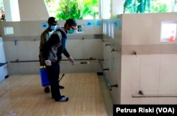 Seorang petugas menyemprotkan cairan desinfektan di tempat wudhu di salah satu masjid sekitar Balai Kota Surabaya (Foto: VOA/ Petrus Riski).