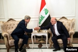 U.S. Secretary of State John Kerry, left, and new Iraqi Prime Minister Haider al-Abadi shake hands after a meeting in Baghdad Sept. 10, 2014.