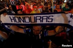 FILE - A demonstrator holds up a scarf during a march to demand the resignation of Honduras' President Juan Orlando Hernandez in Tegucigalpa, Sept. 11, 2015.