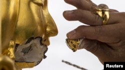 Một người thợ sửa chữa bức tượng thần Hindu Brahma bị hư hại trong vụ nổ tại đền Erawan ở Bangkok, Thái Lan, ngày 26/8/2015.