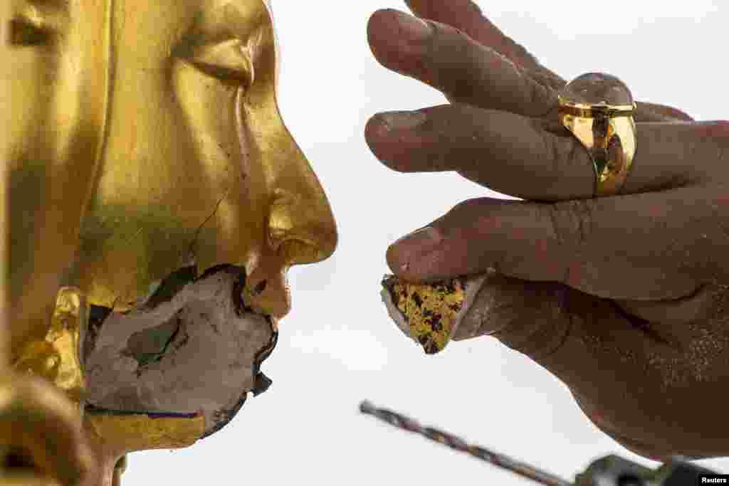 Seorang pengrajin memperbaiki patung Dewa Budha Brahma yang rusak akibat ledakan bom di kuil Erawan di Bangkok, Thailand.