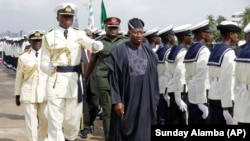 FILE - Nigeria President Goodluck Jonathan inspects the honor guard at a naval warship commissioning event in Lagos, Feb. 19, 2015.