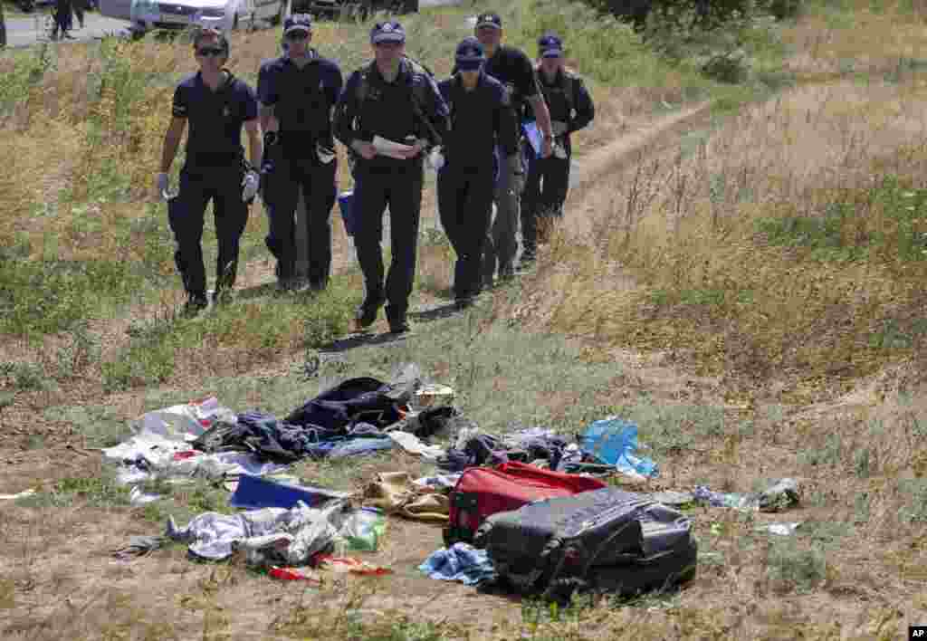 Australian investigators examine the area of the Malaysia Airlines plane crash in the village of Hrabove, Donetsk region, eastern Ukraine, Aug. 1, 2014.