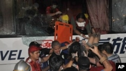 A paramedic (top) lowers one of the wounded survivor from the hijacked bus in Manila, 23 Aug 2010