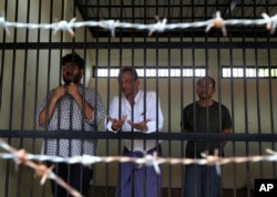 FILE - Aung Naing Soe, left, Burmese freelance journalist and interpreter; Hla Tin, Burmese driver; and Lau Hon Meng, Singaporean journalist stand for their first court appearance after being accused of flying drones illegally over parliament buildings, in Naypyitaw, Myanmar, Nov. 10, 2017.