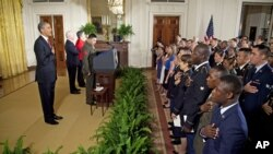 President Barack Obama says the Pledge of Allegiance during a naturalization ceremony for active duty service members in the East Room of the White House, July 4, 2012.