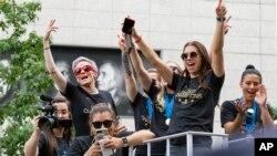 Integrantes del equipo femenino de fútbol de EE.UU. incluyendo Megan Rapinoe, (al fondo a la izquierda), y Alex Morgan, (en el fondo a la derecha) se desplazan en una carroza durante un desfile en la ciudad de Nueva York el miércoles, 10 de julio de 2019.