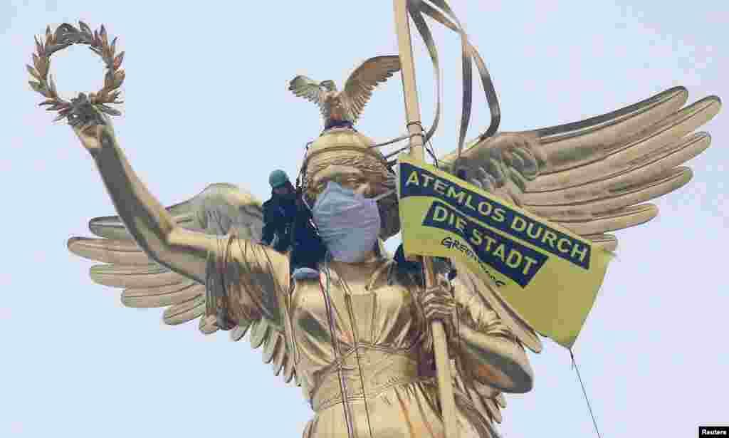 """اعتراض گروه غیر دولتی صلح سبز به آلودگی هوای برلین روی بنایی «پیروزی» در این شهر. روی پرچم شان نوشته اند: """"بی نفس در شهر."""""""