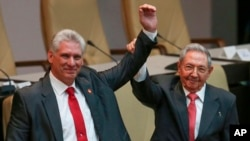 Cuba's outgoing President Raul Castro, right, and new President Miguel Diaz-Canel raise their arms in unison at the National Assembly in Havana, Cuba, April 19, 2018.
