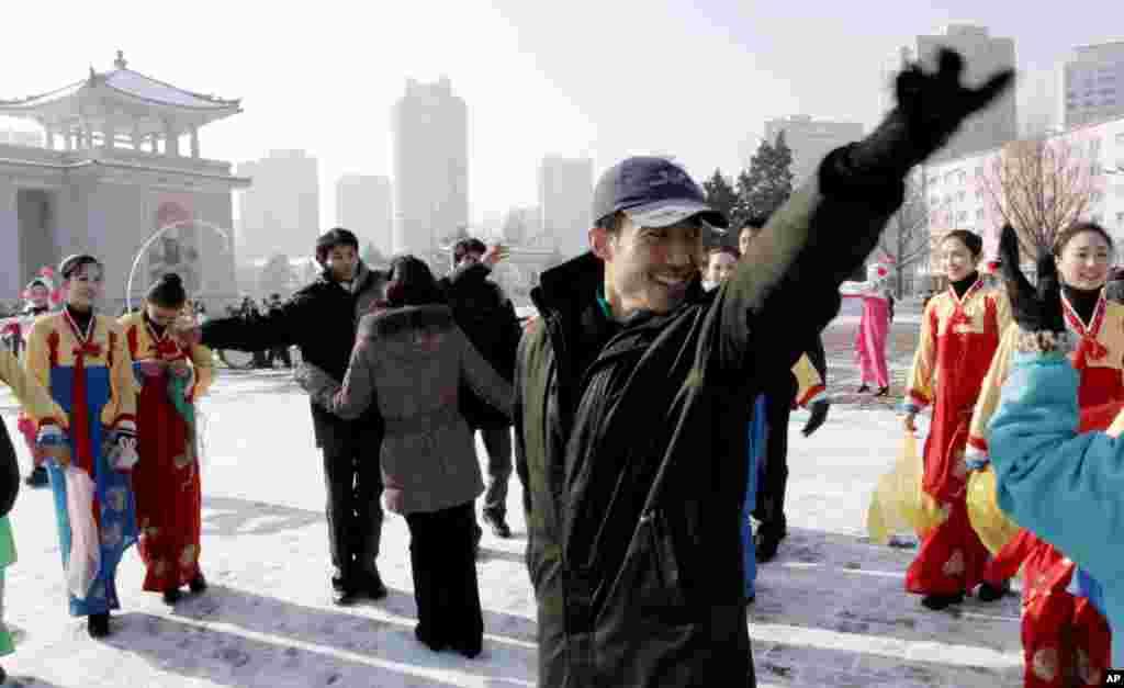 Đoàn viên thanh niên Bắc Triều Tiên ca múa trước Nhà hát lớn Bình Nhưỡng để ăn mừng vụ phóng. (AP Photo/Jon Chol Jin)