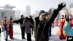Warga Korea Utara meluapkan kegembiraan mereka atas keberhasilan peluncuran roket mereka dengan menari di depan Pyongyang Grand Theater di Pyongyang, Korea Utara (12/12). Para analis memperkirakan hanya sedikit hal yang dapat dilakukan masyarakat Internasional untuk mengontol perilaku Korea Utara pasca keberhasilan peluncuran ini.