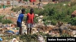 Crianças despejam o lixo em lixeira a céu aberto em Malanje