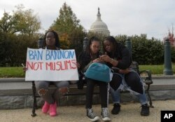 Trump Protests Washington: Washington area high school students sitting on a park bench, from left, Makeda Lydia, 14, Sarah Tewodros, 14 and Serwah Lydia, 17, protest on Capitol Hill in Washington, Nov. 15, 2016.