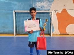 Salah satu anak disabilitas siswa SLB menunjukkan piala dan sertifikat pemain terbaik dalam SLB Futsal Festival di Bandung, Februari 2018 (foto: VOA/Rio Tuasikal)