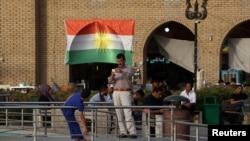 FILE - A man takes a photo of his son near the castle market of Erbil, Iraq, Aug. 17, 2017.
