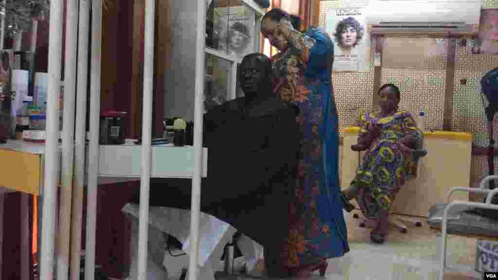 Mata na hobbasa wajen yin sana'o'i a Nijar. Anan mace kewa na maza aski a Niamey, 14 ga Satumba, 2014.