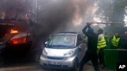戴着面罩的示威者在巴黎抗议活动中砸汽车烧汽车。(2018年12月2日)