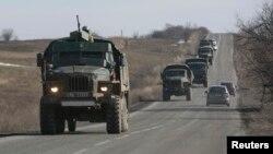"""Pejuang separatis yang menamakan diri mereka tentara """"Republik Rakyat Donetsk"""" menarik diri dari garis depan dan mengangkut meriam di belakang truk militer mereka menuju kota Donetsk (23/2)."""