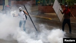 An anti-government protester throws a tear gas canister back at police during a protest against President Nicolas Maduro's government in Caracas, May 8, 2014.