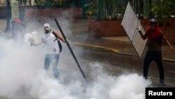 Seorang demonstran anti pemerintah melempar kembali tabung gas air mata ke arah polisi dalam protes anti pemerintahan Presiden Nicolas Maduro di Caracas, 8/5/2014.