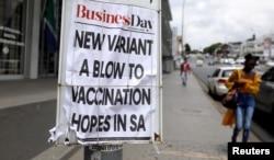 FILE - A woman walks past newspaper billboards during the coronavirus disease (COVID-19) outbreak in Johannesburg, South Africa, Feb. 8, 2021.