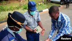 Un policier montre à un visiteur comment désinfecter ses mains contre la propagation de la maladie à coronavirus au palais présidentiel à Harare, Zimbabwe, le 19 mars 2020. (REUTERS/Philimon Bulawayo)