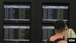 Salah satu penumpang Qantas memandangi pengumuman penerbangan di Bandara Internasional Sydney, Minggu (30/10). Qantas membatalkan semua penerbangan mulai Sabtu karena aksi mogok para pekerjanya.