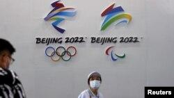 一名戴着口罩的妇女走过北京的国际服务贸易交易会悬挂的2022年冬季奥运会和冬季残奥会标识。(2021年9月3日)